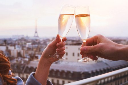 Cheers with two champagne glasses on a trip to Paris