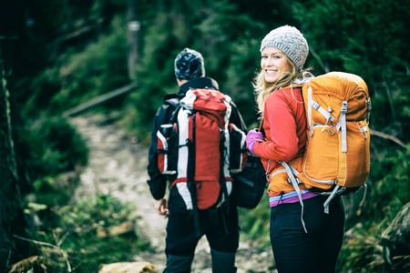woman and man hiking with backpacks