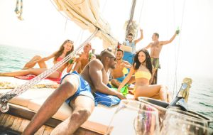 group of multiracial friends having fun at sail boat party with dj set - friendship concept with young multi racial people on sailboat - travel lifestyle on exclusive vibe mood - warm bright filter